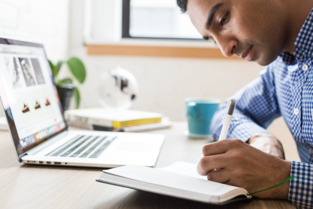 Man writing in notebook with laptop in the background