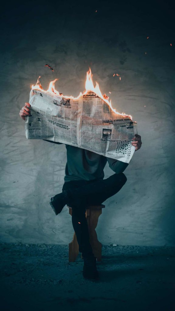 man sitting on stool holding newspaper on fire