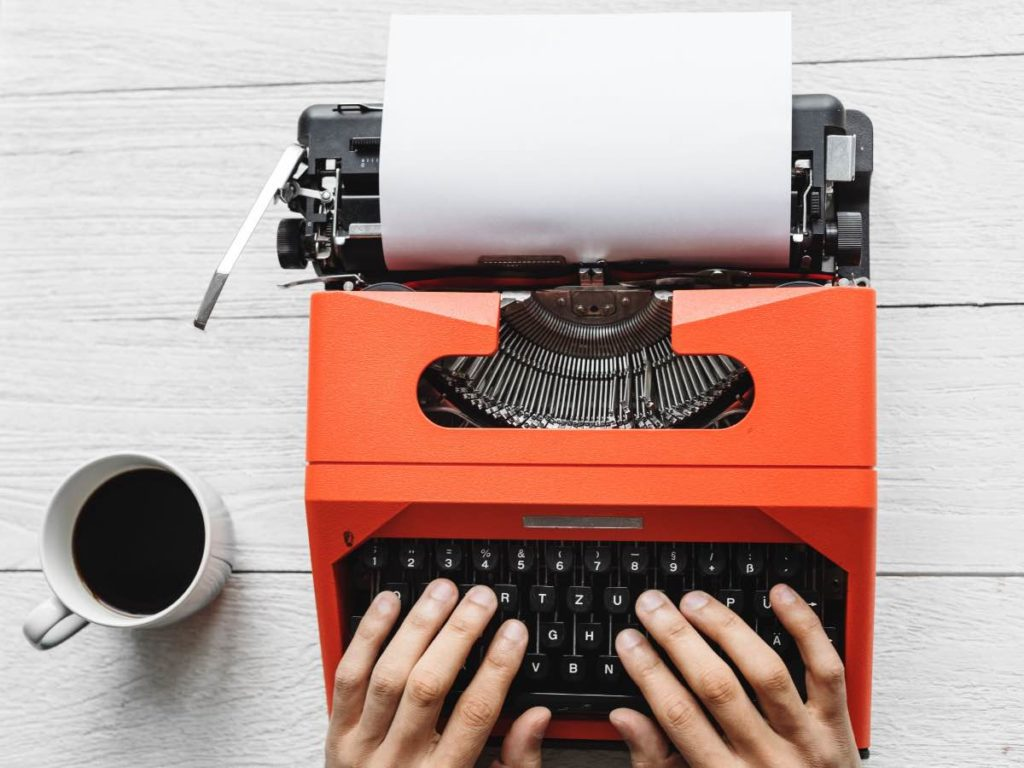 person copywriting and content writing on orange typewriter with mug of coffee on white desk