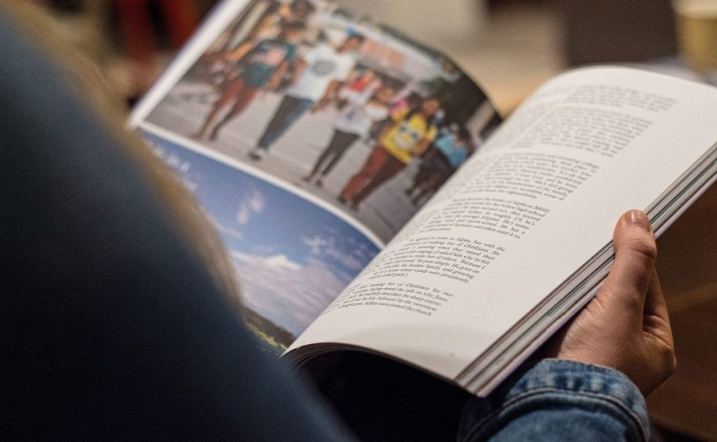 person looking at traditional advertising in a magazine