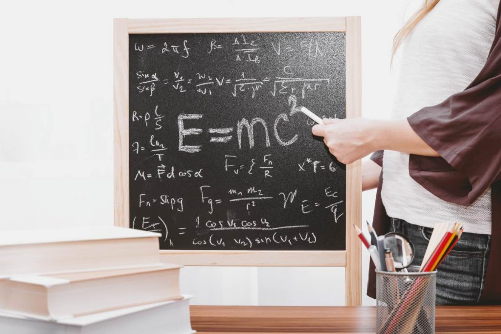 chalkboard with E=mc2 and someone pointing with a piece of chalk