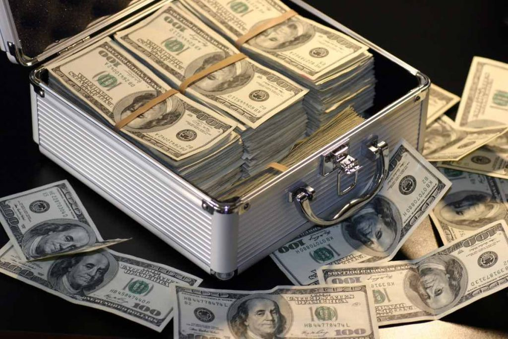 open metal case with stacks of 100 dollar bills inside and outside