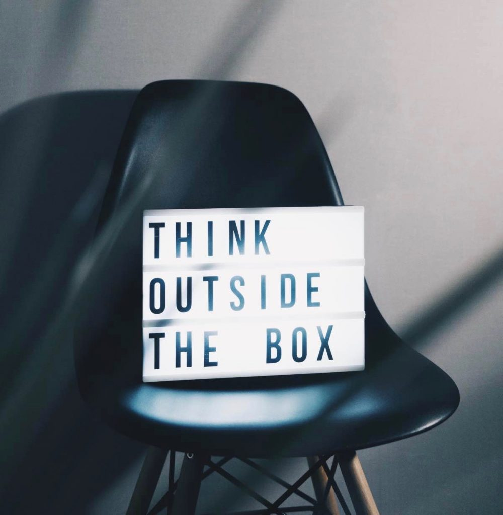 think outside the box sign placed on black chair